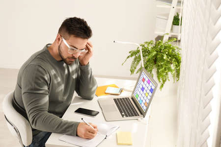 Young man using calendar app on laptop in office