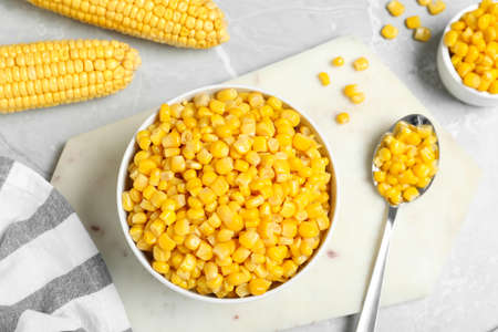 Delicious canned corn in bowl on marble table, flat lay