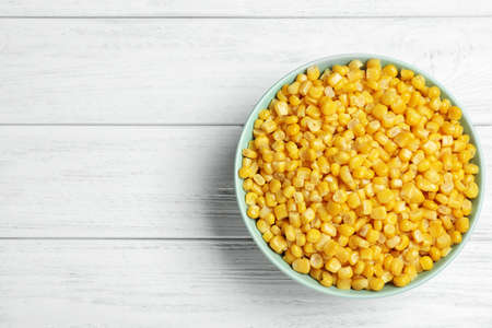 Delicious canned corn in bowl on white wooden table, top view. Space for text Banco de Imagens