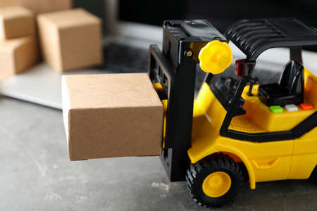Toy forklift with box near laptop on table. Logistics and wholesale concept