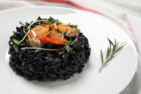 Delicious black risotto with seafood in plate, closeup