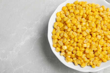Delicious canned corn in bowl on marble table, top view. Space for text