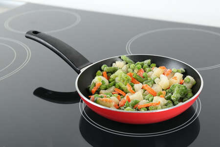 Cooking tasty frozen vegetable mix on induction stove Stock Photo