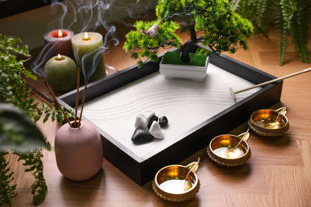 Beautiful miniature zen garden, incense sticks and oil lamps on table Stock Photo