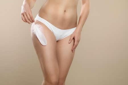 Woman with feather showing smooth skin on beige background, closeup. Brazilian bikini epilation