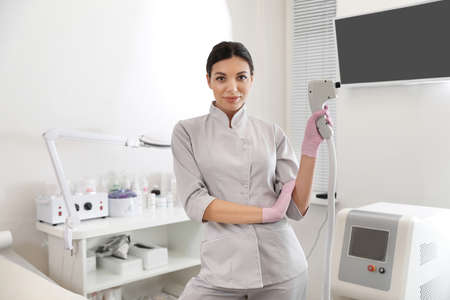 Young woman holding professional laser epilator in beauty salon Stock fotó
