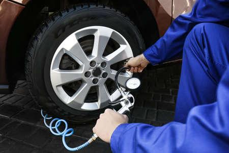 Meccanico che controlla la pressione dell'aria dei pneumatici al servizio dell'auto, primo piano