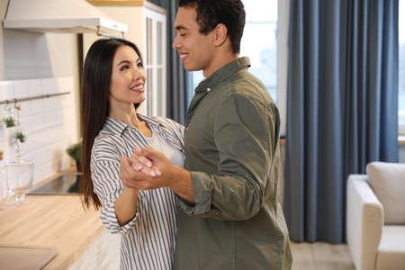 Encantadora joven pareja interracial bailando en casa Foto de archivo