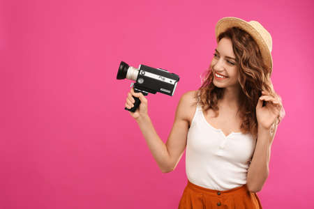 Beautiful young woman with vintage video camera on crimson background, space for text