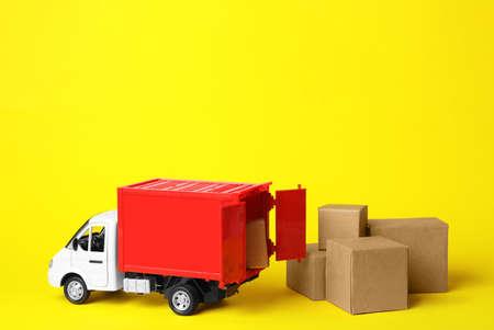 Camión de juguete con cajas sobre fondo amarillo. Concepto de logística y venta al por mayor Foto de archivo