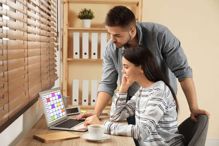 Colleagues working with calendar app on laptop in office Stock Photo