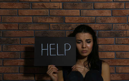 Abused young woman with sign HELP near brick wall. Domestic violence concept