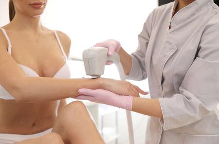Young woman undergoing laser epilation procedure in beauty salon, closeup