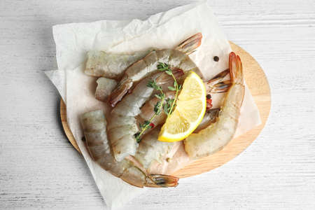 Fresh raw shrimps on white wooden table, top view