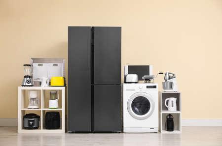 Nowoczesna lodówka i inne urządzenia gospodarstwa domowego w pobliżu beżowej ściany w pomieszczeniu