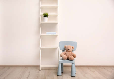 Teddy bear on chair and shelving unit near wall in child room Foto de archivo