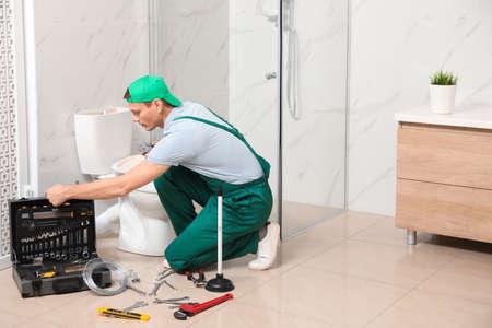 Professional plumber repairing toilet tank in bathroom