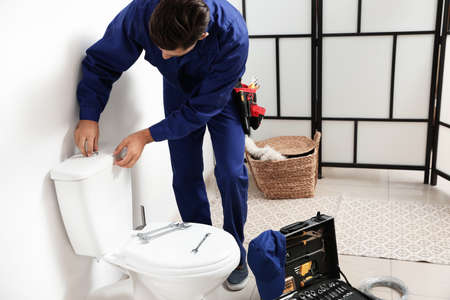 Professional plumber working with toilet bowl in bathroom