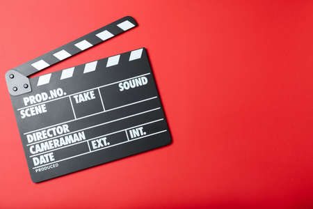 Clapper board on red background, top view with space for text. Cinema production