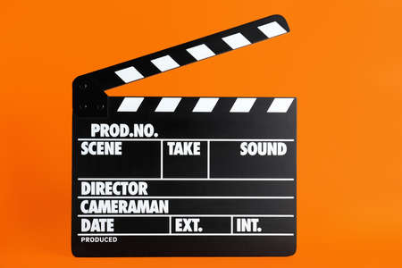 Clapper board on orange background. Cinema production Stockfoto