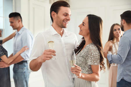 Lovely young couple with glasses of champagne at dancing party