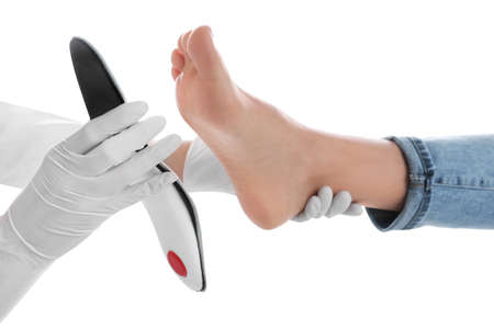 Orthopedist fitting insole on patient's foot against white background, closeup