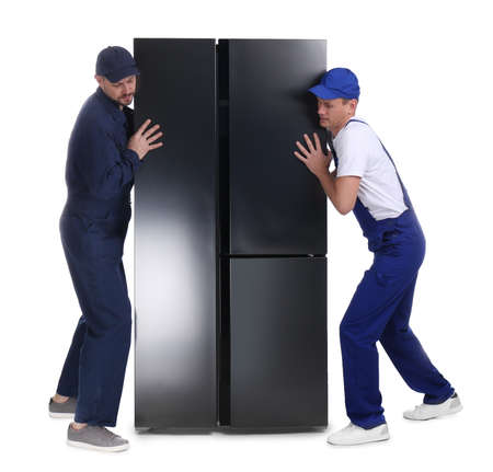 Professional workers carrying refrigerator on white background