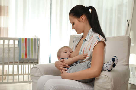 Woman breastfeeding her little baby at home