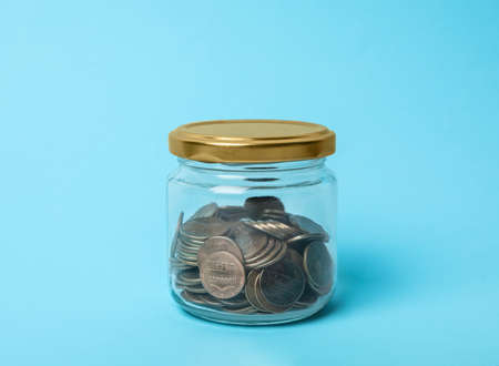 Glass jar with coins on light blue background Stock Photo
