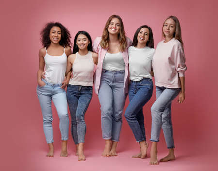 Group of women with different body types on pink background