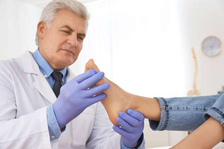 Male orthopedist checking patient's foot in clinic