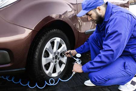 Mechanic checking tire air pressure at car service Foto de archivo