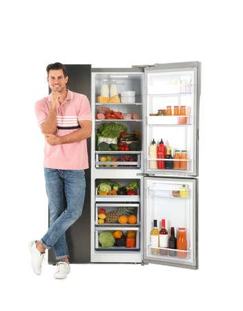 Mann nahe offenem Kühlschrank auf weißem Hintergrund