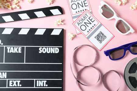 Flat lay composition with cinema tickets and clapperboard on pink background