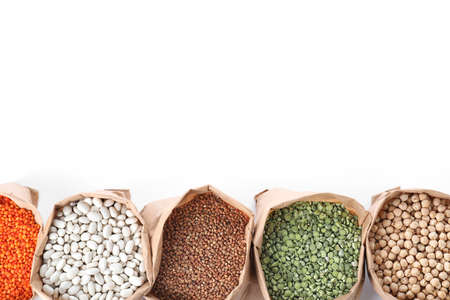 Different types of legumes  and cereals in paper bags on white background, top view. Organic grains