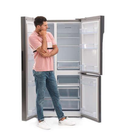 Mann nahe leerem Kühlschrank auf weißem Hintergrund