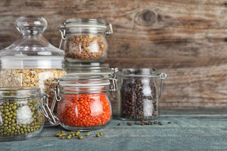 Different types of legumes and cereals in glass jars on blue wooden table, space for text. Organic grains