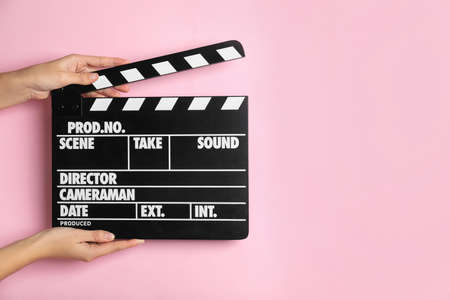 Woman holding clapperboard on pink background, closeup with space for text. Cinema production