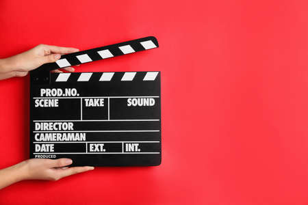 Woman holding clapperboard on red background, closeup with space for text. Cinema production