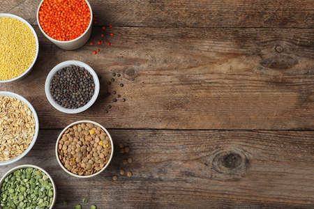 Flat lay composition with different types of legumes and cereals on wooden table, space for text. Organic grains