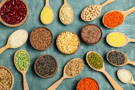 Flat lay composition with different types of legumes and cereals on blue wooden table. Organic grains