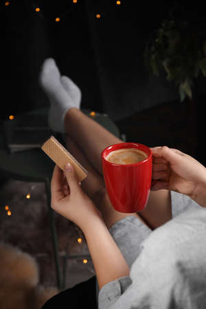 Woman with wafer and coffee on dark background, closeup. Early breakfast Фото со стока
