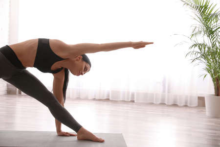 Young woman practicing triangle asana in yoga studio. Utthita Trikonasana pose
