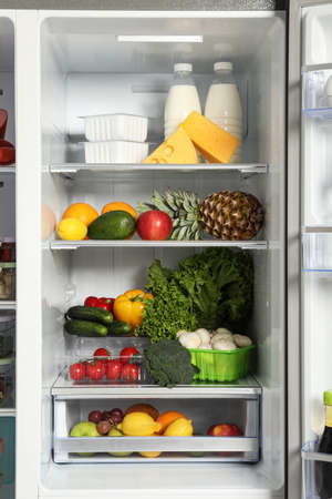 Otwarta lodówka pełna różnych świeżych produktów