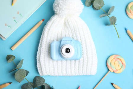 Flat lay composition with toy camera on light blue background. Future photographer Stock Photo