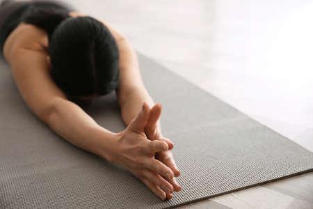 Young woman practicing extended child's asana in yoga studio, closeup. Utthita Balasana pose
