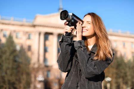 Beautiful young woman with vintage video camera on city street