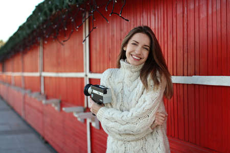 Beautiful young woman with vintage video camera outdoors