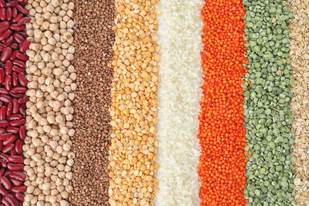 Different types of legumes and cereals as background, top view. Organic grains