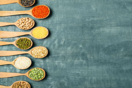 Flat lay composition with different types of legumes and cereals on blue wooden table, space for text. Organic grains